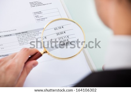 Businessman Looking At Document Through Magnifying Glass - stock photo