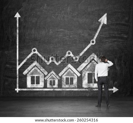 businessman looking at drawing real estate icons and chart - stock photo