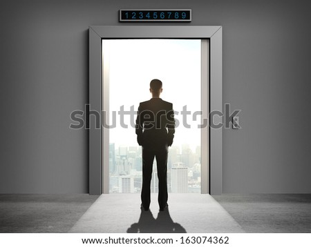 businessman looking at elevator to city