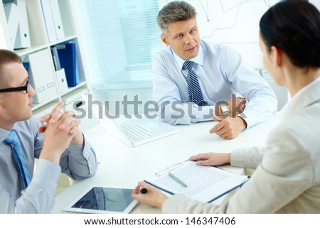Businessman looking at his employee while explaining his idea - stock photo