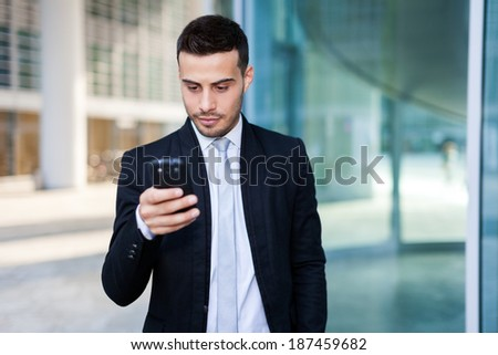 Businessman looking at his phone - stock photo