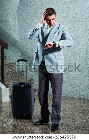 Businessman looking at his watch, he is going to be late - stock photo