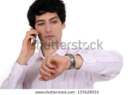 Businessman looking at his watch while taking a call - stock photo