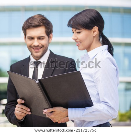 Businessman looking at paperwork with businesswoman. Businessman and woman looking at black folder  - stock photo