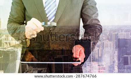 Businessman looking at tablet with magnifying glass against new york - stock photo
