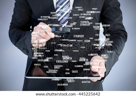 Businessman looking at tablet with magnifying glass against sphere of skills - stock photo