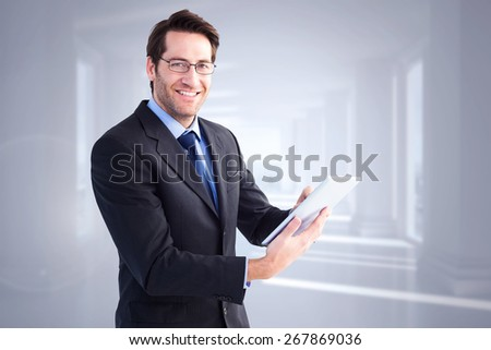 Businessman looking at the camera while using his tablet against bright white hall with columns - stock photo