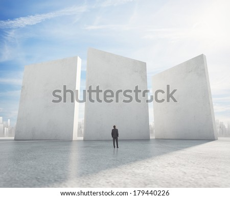 Businessman looking at three cement blank banners and city on horizon - stock photo