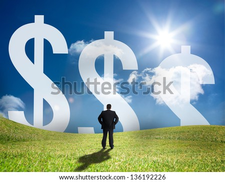 Businessman looking at three large dollar signs on the horizon and standing in a sunny field - stock photo