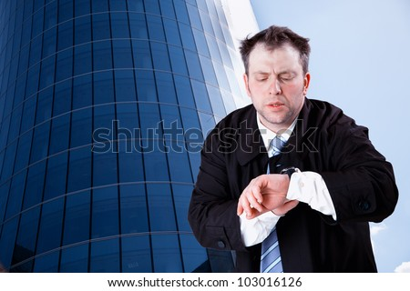 Businessman looking at wristwatch - stock photo