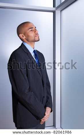 Businessman looking calm and peaceful, relaxing near a window.