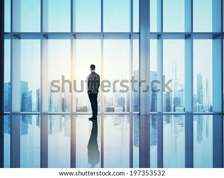 Businessman looking city through window  - stock photo