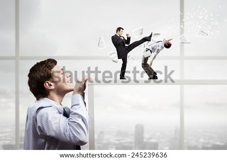 Businessman looking from under table at two fighting colleagues - stock photo