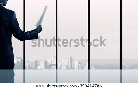 Businessman looking in papers against office window
