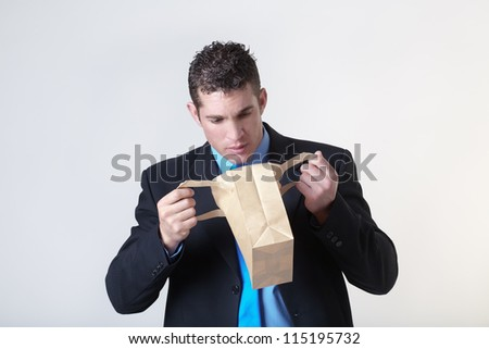 businessman looking into a paper bag to see what he can find - stock photo