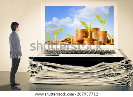 Businessman looking Money, Trees,Coins, Business growing concept, Success, Young tree growing on coins stack and Blue Sky on computer laptop and newspaper - stock photo