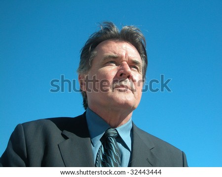 Businessman looking off in the distance. Perfect sky. - stock photo
