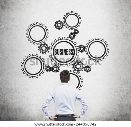 businessman looking on drawing gears with business icons - stock photo