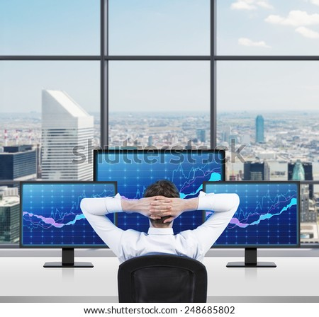 businessman looking on stock graph on three monitors - stock photo