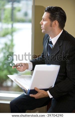 Businessman looking out office window holding binder - stock photo