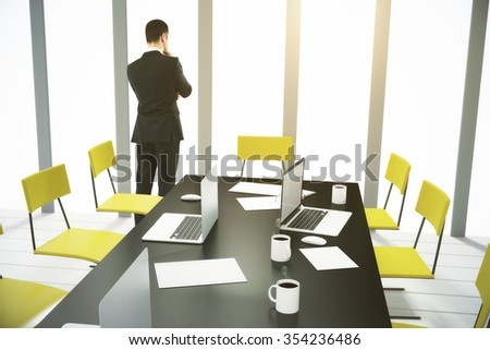 Businessman looking out the window in conference room with furniture and laptops 3D Render - stock photo