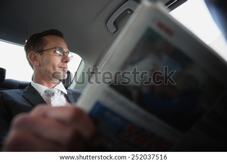 Businessman looking out the window in his car - stock photo