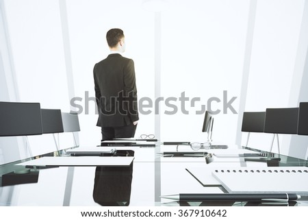 Businessman looking out the window in modern conference room with glassy table  - stock photo