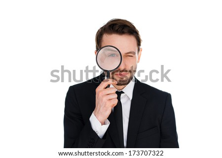 Businessman looking through a magnifying glass directly at the camera with an enlarged eye in a conceptual image, isolated on a white background - stock photo