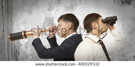 Businessman looking through binoculars - stock photo