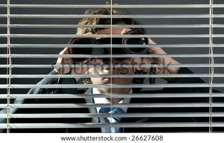 Businessman looking through binoculars behind a blinds window - stock photo