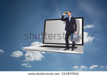 Businessman looking through binoculars holding briefcase against cloudy sky with sunshine - stock photo