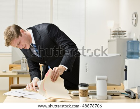 Businessman looking through file folders - stock photo
