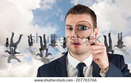 Businessman looking through magnifying glass against blue sky with white clouds - stock photo