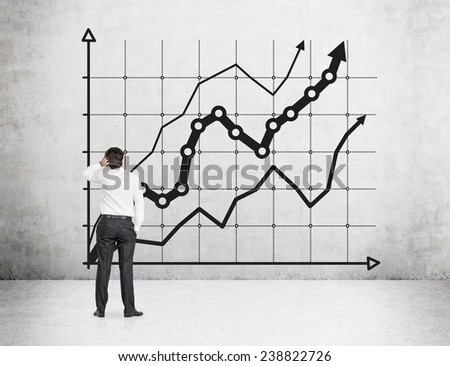 businessman looking to chart on concrete wall