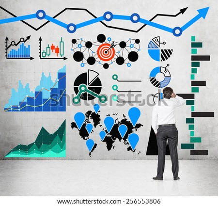 businessman looking to drawing chart and arrows on wall - stock photo