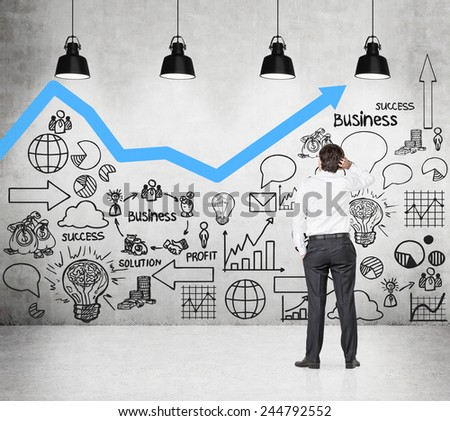 businessman looking to drawing scheme on wall - stock photo