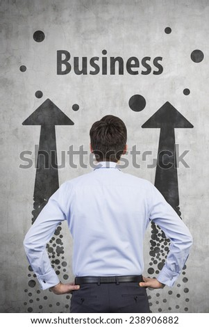 businessman looking to drawing two arrows on wall - stock photo
