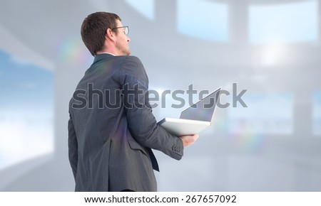 Businessman looking up holding laptop against bright white room with windows