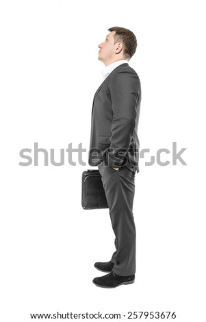 Businessman looking up with his hand in his pocket. Over white.  - stock photo