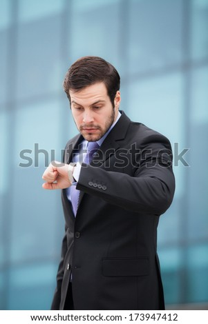 businessman looking very confused to his watch - stock photo