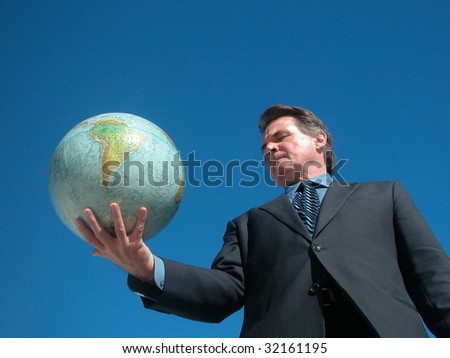 Businessman looks at area on globe - stock photo