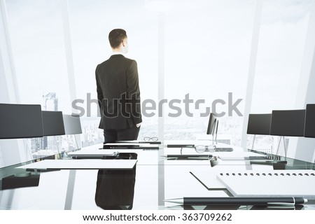 Businessman looks out the window in conference room with glassy table and chairs - stock photo