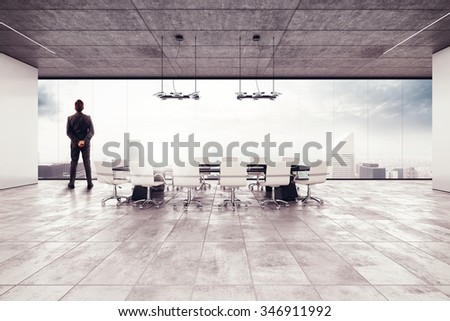 Businessman looks the view from meeting room - stock photo