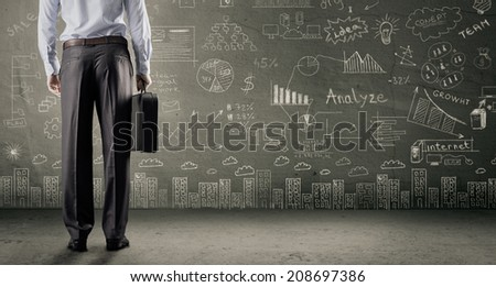 Businessman looks through a hole in a concrete wall in the future - stock photo