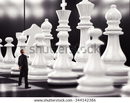 Businessman looks up to big chess pawn