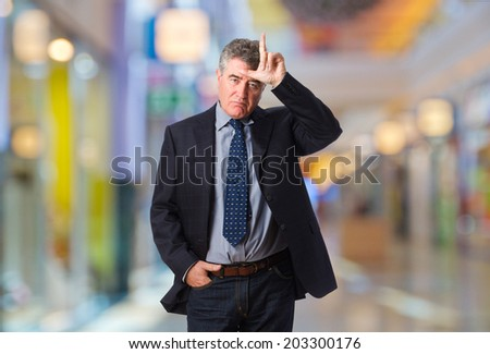 businessman loser gesture in a shopping center - stock photo