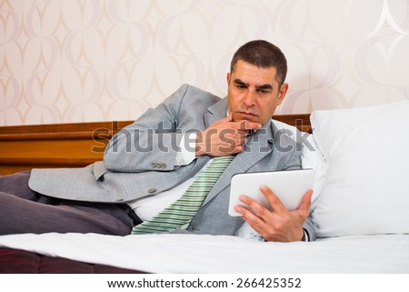 Businessman lying in bed using digital tablet