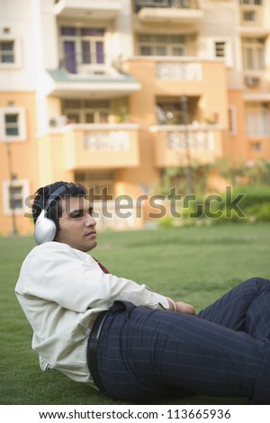 Businessman lying on the grass and listening to music - stock photo