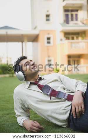 Businessman lying on the grass and listening to music