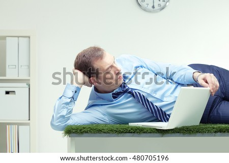 Businessman lying on the grass table with laptop